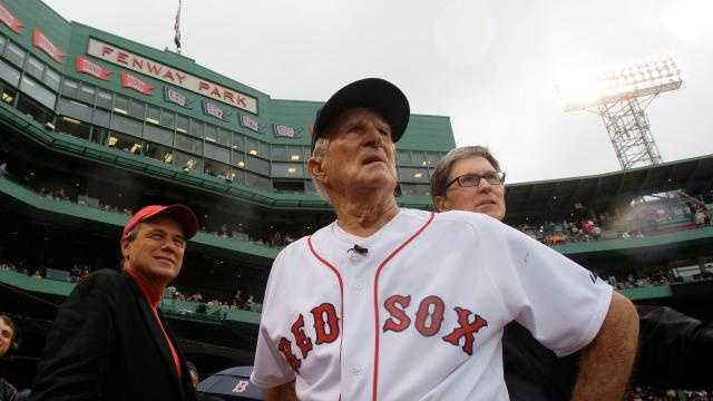 Boston Red Sox great Johnny Pesky, center, is flanked by team president Larry Lucchino, left, and owner John Henry as they look past Pesky's Pole where Pesky's No. 6 adorns the upper deck during a ceremony to retire his number prior to a baseball game against the New York Yankees at Fenway Park in Boston, Sunday Sept. 28, 2008.