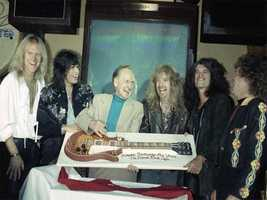 Guitar designer Les Paul, third from left, is accompanied by members of the rock group Aerosmith as Paul celebrates his 75th birthday with a party at New York's Hard Rock Cafe, Monday, June 12, 1990. Posing with a cake shaped like a Gibson 'Les Paul' model guitar are, from left, Tom Hamilton, Steven Tyler, Paul, Brad Whitford, Joe Perry and Joey Kramer.
