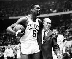 Russell is congratulated by coach Red Auerbach after scoring his 10,000th point in the game against the Baltimore Bullets Dec. 12, 1964.