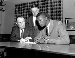 Bill Russell signs the contract with the Boston Celtics on Dec. 19, 1956. Seated at left is Celtics co-owner and president Walter Brown, and standing behind him is co-owner Lou Pieri.