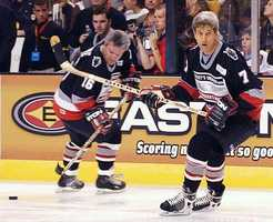 Kerry heads up the ice followed by retired NHL player Marcel Dionne during the annual charity hockey game to benefit the Leary Firefighters Foundation, Sept. 28, 2003,