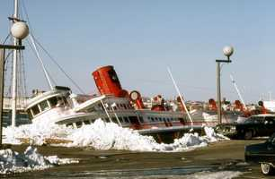 The sidewheeler Peter Stuyvesant, which formed part of Anthony's Pier Four Restaurant, was torn from its concrete pilings and wrecked in Boston Harbor.