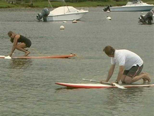Fitness Instructor Anne Marie Leahy teaches Anthony, paddleboard basics.