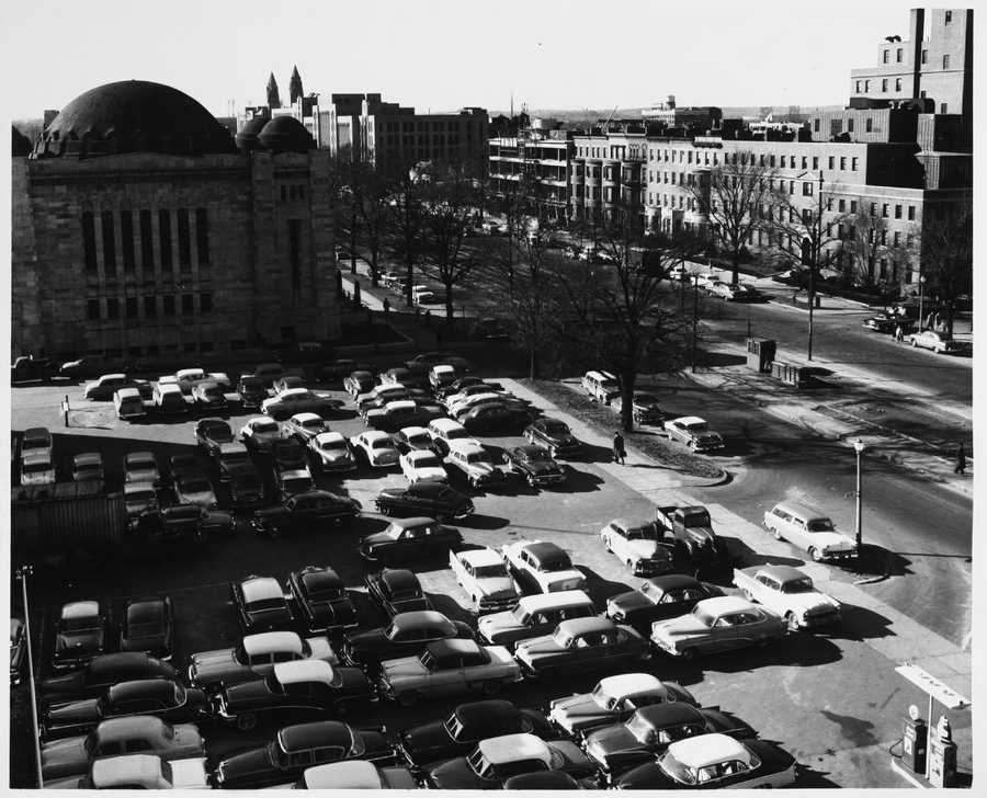 A view of the Texaco Station parking lot next To Temple Adath Israel (Alfred A. Morse Auditorium) on Commonwealth Avenue near Kenmore Square in 1957. Boston University can be seen in the background.