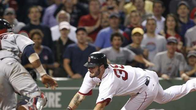 Boston Red Sox's Jarrod Saltalamacchia dives for home plate to score the winning run as Cleveland Indians catcher Carlos Santana tries to tag him in the ninth inning of a baseball game at Fenway Park in Boston Tuesday, Aug. 2, 2011. The Red Sox won 3-2.