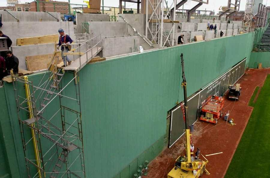 "Now the wall is famous. Here, construction workers install the scoreboard and seats on top of the ""Green Monster"" in April 2003."