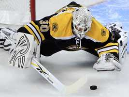 Boston Bruins goalie Tim Thomas dives on the puck for a save against the Florida Panthers.