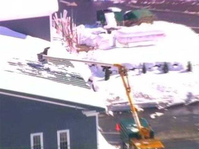 A man clears snow off a roof in Central Massachusetts