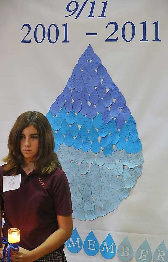 On the 10th anniversary of Sept. 11, Ashley Rose-Marrzelli, an 8th grader at Taunton Catholic Middle School, holds a candle in front of the TCMS tear drop.