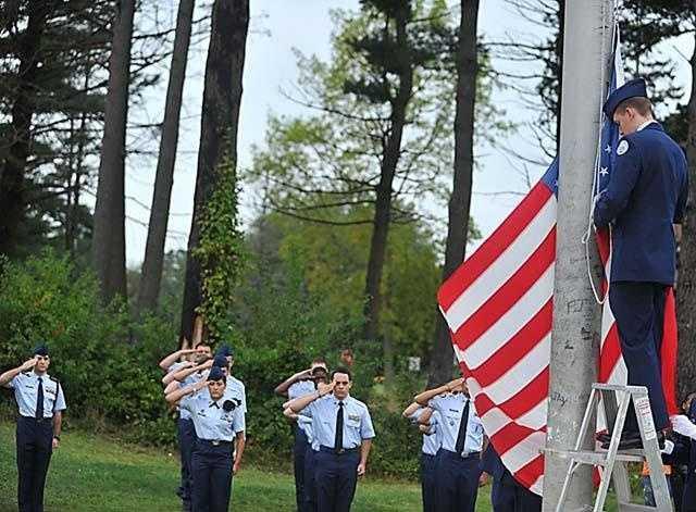 Cadet Zachary Ostenson raises the flag to half staff at the Taunton High School 9/11 memorial service.