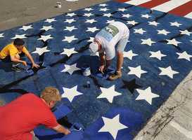 Alan Road residents Jack Chaves, 10, left, Ryan Leahy, 14, bottom , and Tom Leahy, right, repaint the American flag.