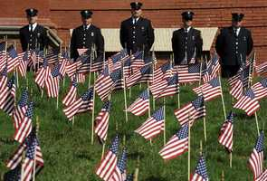 Firefighters and police officers stand in between the Walker Building and 3,000 flags during 9/11 ceremonies in Marlborough.