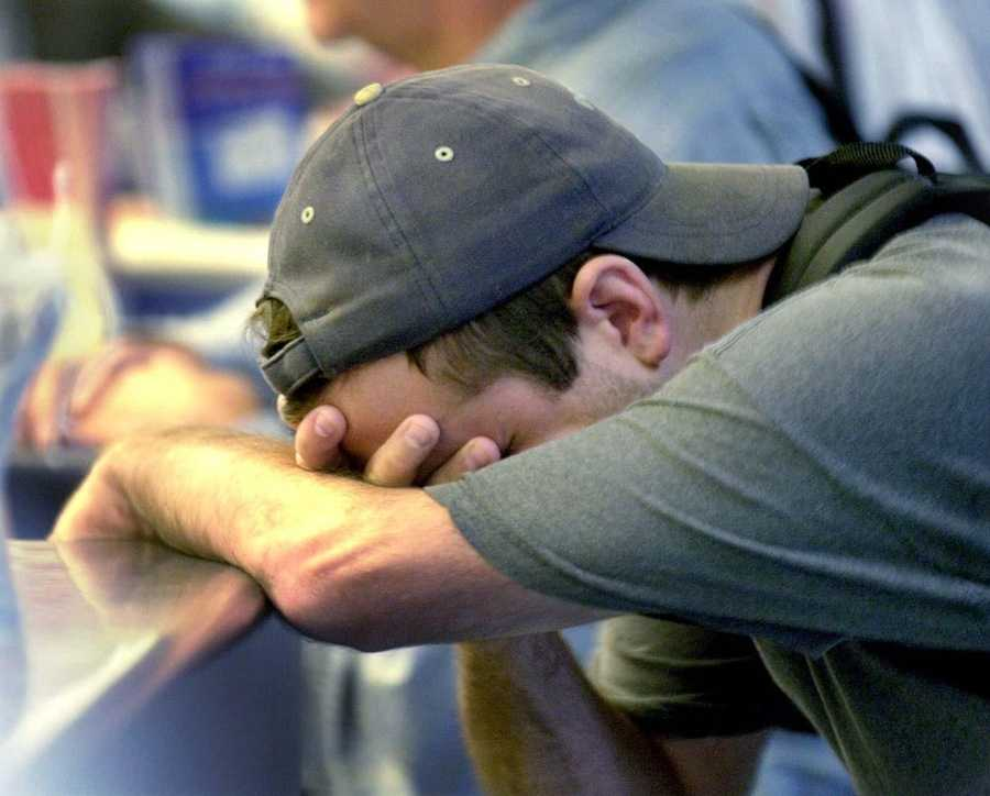 Craig McFarland holds his head at the ticket counter of American Airlines. McFarland, who exchanged his ticket, says he was supposed to leave on American Flight 11 which left Boston and crashed into the World Trade Center.