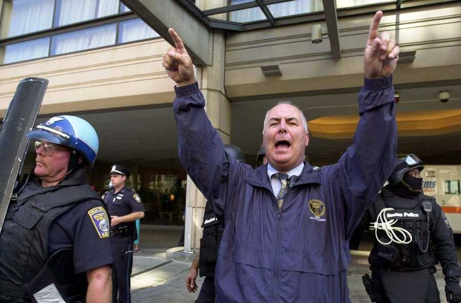 A Boston police officer gestures for people to clear the entrance to the Westin Hotel in Boston, Sept. 12, 2001 as officers and SWAT team members leave after a team of FBI agents searched for suspects.