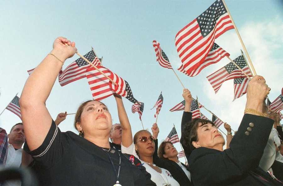 American Airlines employees Luisa Arias, of Revere, and Mary Grace Rubino, of Wakefield, wave American flags during an interfaith vigil of prayer and solidarity at Boston City Hall, Sept. 13, 2001.