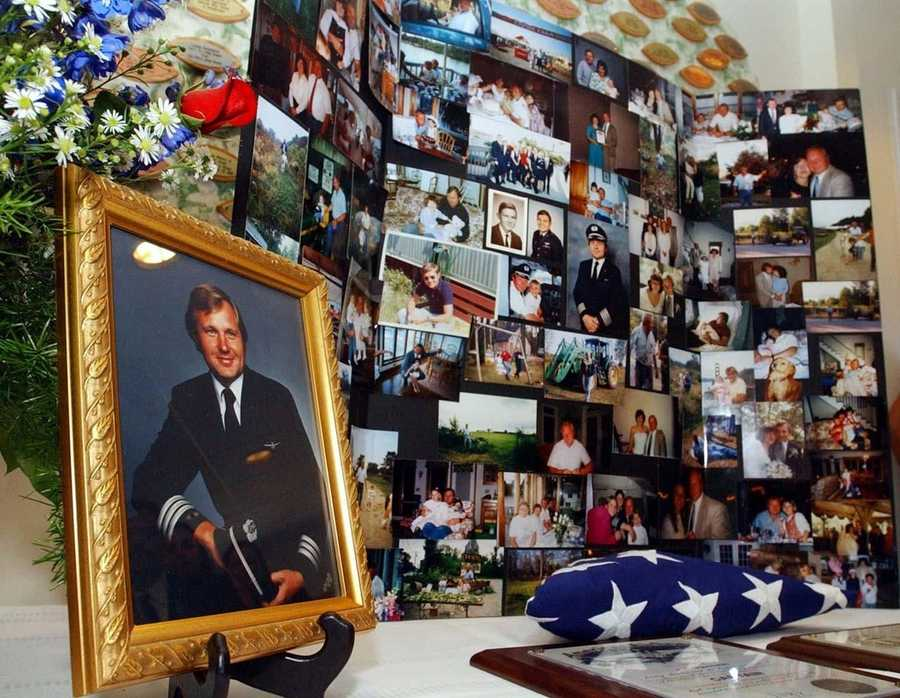 A portrait pilot John Ogonowski sits on a table surrounded by a photo memorial, plaques and a folded American flag at a memorial service at St. Francis Church in Dracut.