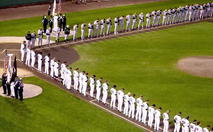 The Boston Red Sox and the Tampa Bay Devil Rays line up on the baselines and bow their heads during a brief memorial ceremony before the start of the game, Sept. 18, 2001, in Boston.