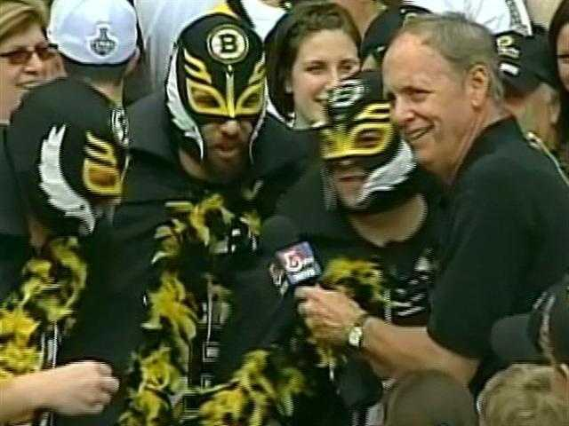 "Mike Dowling talks to the masked ""Lucicadors"" before the Bruins championship rally after winning the Stanley Cup."