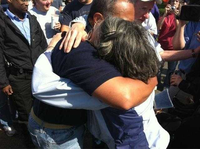 A woman sobs as Gov. Deval Patrick gives her a hug