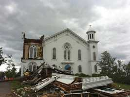 The clock face of the destroyed First Church of Monson lying on the ground.