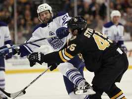 Boston Bruins defenseman Mark Stuart checks Toronto Maple Leafs right wing Colton Orr during the first period of an NHL hockey game in Boston on Thursday, Oct. 28, 2010.