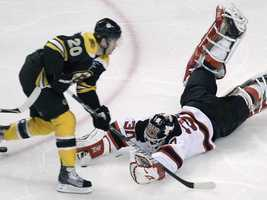 New Jersey Devils goalie Martin Brodeur, right, dives out from the crease as he makes a save on a shot by Boston Bruins left wing Daniel Paille during the first period of an NHL hockey game in Boston, Monday, Nov. 15, 2010.