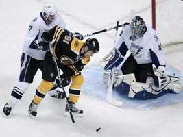 Boston Bruins center Marc Savard (91) shoots a backhander towards Tampa Bay Lightning goalie Mike Smith, right, who drops for the save, during the first period of their NHL hockey game in Boston, Thursday, Dec. 2, 2010. Lightning defenseman Brett Clark, left, looks on.