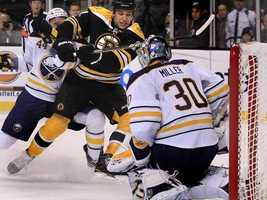 Boston Bruins left wing Milan Lucic, center, gets past Buffalo Sabres Andrej Sekera, rear left, as he shoots on goalie Ryan Miller during the second period of an NHL hockey game in Boston, Tuesday, Dec. 7, 2010.