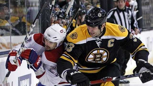 Boston Bruins defenseman Zdeno Chara (33) checks Montreal Canadiens right wing Brian Gionta (21) against the boards as they chase the puck during the first period of an NHL hockey game in Boston, Wednesday, Feb. 9, 2011.