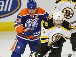 Boston Bruins Johnny Boychuk, front, blocks a shot as Edmonton Oilers' Oiler Shawn Horcoff, left, looks on during the first period of an NHL hockey game in Edmonton on Sunday, Feb. 27, 2011.