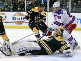 Boston Bruins goalie Tuukka Rask (40), of Finland, smothers the puck between his legs as New York Rangers' Wojtek Wolski (86), of Poland, looks for a rebound during the first period of an NHL hockey game, Saturday, March 26, 2011, in Boston.