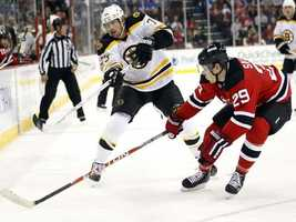 Boston Bruins right wing Michael Ryder, left, and New Jersey Devils defenseman Anssi Salmela (29), of Finland, chase a puck in the first period of an NHL hockey game on Sunday, April 10, 2011, in Newark, N.J.