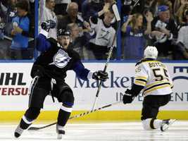 Tampa Bay Lightning's Steven Stamkos celebrates after scoring a goal as Boston Bruins' Johnny Boychuk looks on.