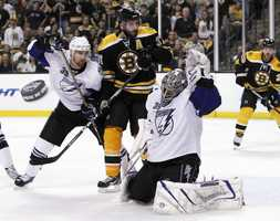 Patrice Bergeron skates into Tampa Bay Lightning goalie Dwayne Roloson as Tampa Bay Lightning defenseman Mike Lundin defends.