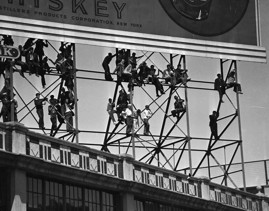 "Forget ""Standing Room Only"" tickets -- these fans opt to dangle from the billboard supports in 1937."