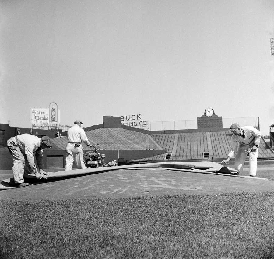 The pitching mound at Fenway Park in Boston is prepared for opening day by some groundskeepers, April 9, 1958. Head groundskeeper Connie Sullivan, right, helps John Coyne remove a tarpaulin while Jim McCarthy mows the grass in the background.