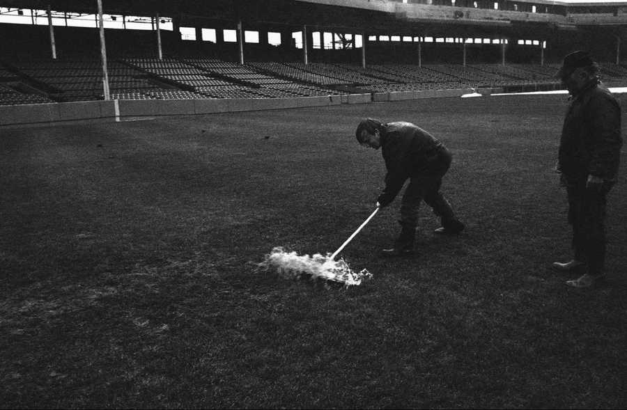 Fenway Park worker shovels water from deep center field Sunday, Oct. 19, 1975. The sixth game of the World Series was postponed for the second time.