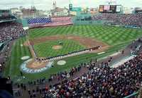 Members of the Boston Red Sox and Toronto Blue Jays line the field as a giant American flag is unveiled over the Green Monster wall before the game at Fenway Park in Boston, on opening day, Monday, April 1, 2002.