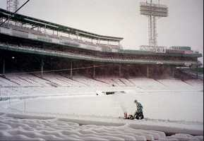 An unidentified grounds worker pushes a snow blower across the infield of Fenway Park.