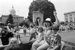 Christa McAuliffe, rides in front of the New Hampshire State House with her daughter Caroline and son Scott.