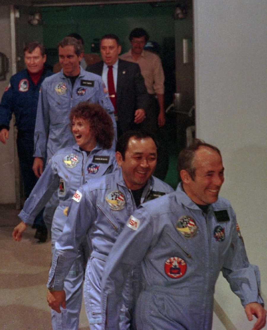 Four crew members of the space shuttle Challenger leave their quarters: Payload specialist Greg Jarvis, mission specialist Ellison Onizuka, Christa McAuliffe and pilot Mike Smith.