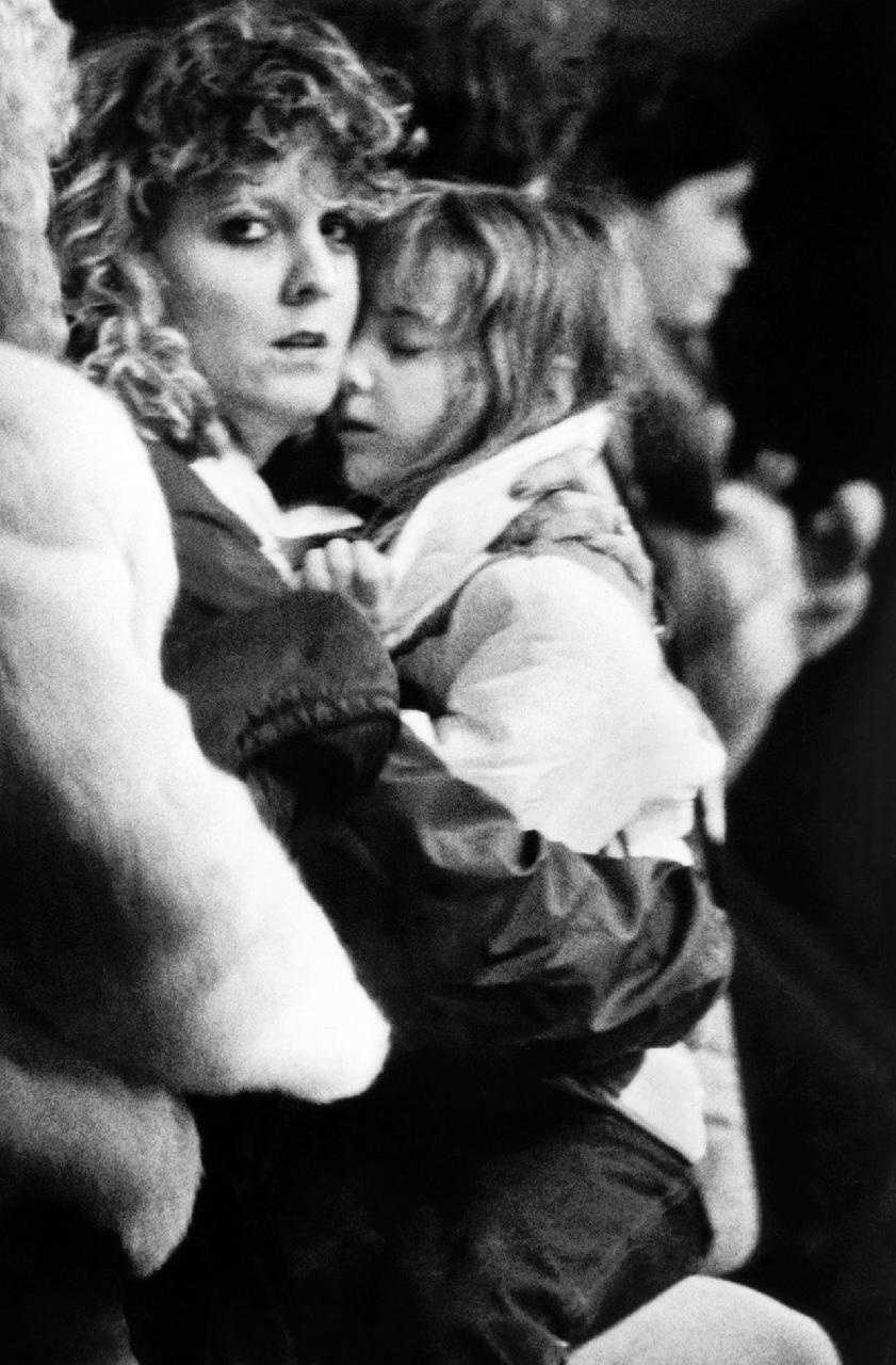 Unidentified woman hugs a child inside the Kimball School in Concord, N.H. after the girl returned from the Kennedy Space Center with a group of classmates.