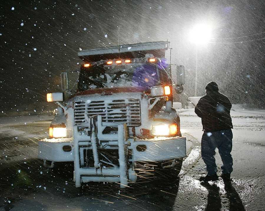 Marshfield DPW plow driver Chuck Davis cleans his headlights while waiting to get a load of sand.