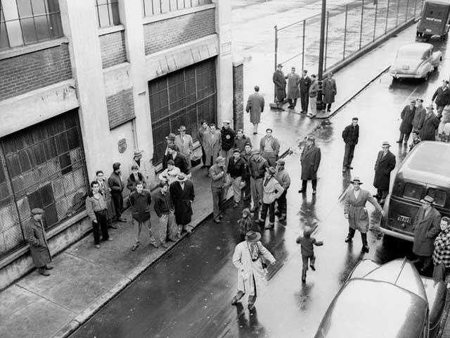 Curious bystanders and a few newsmen gather about the Prince Street entrance to Brinks's Inc., in Boston, Mass Jan. 18, 1950. It was the scene of a $1,500,000 holdup by seven bandits the night before.
