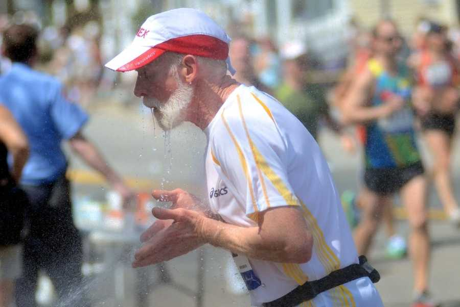 A runner splashes water on his face in Wellesley.