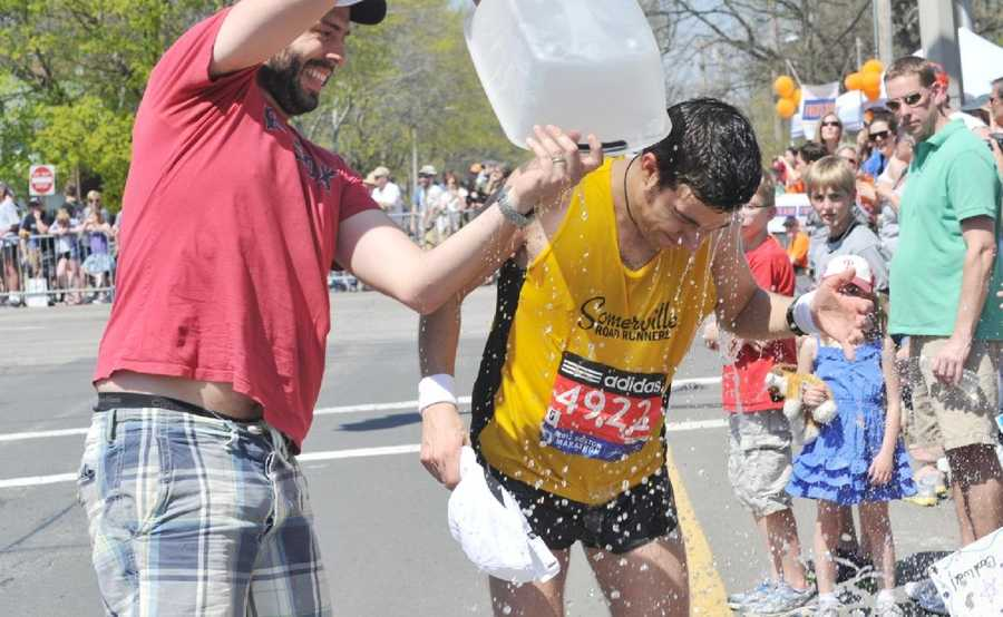 A volunteer dumps water on a runner in Newton.