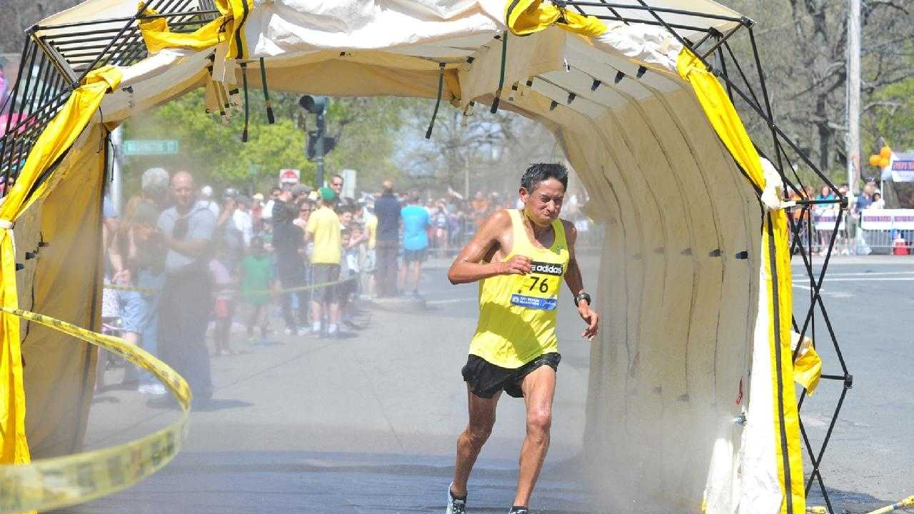 A runner goes through the misting tent in Newton.