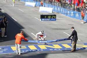Joshua Cassidy, of Canada, crosses the finish line in world record time of1:18:25