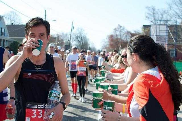 A runner carries a bottle of water win him.