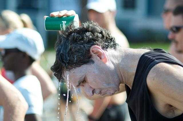 A runner pours water on his head before the race.